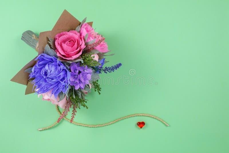 Um ramalhete de flores de papel coloridas e um coração vermelho pequeno em um fundo verde como um contexto para um cartão, letra  fotos de stock