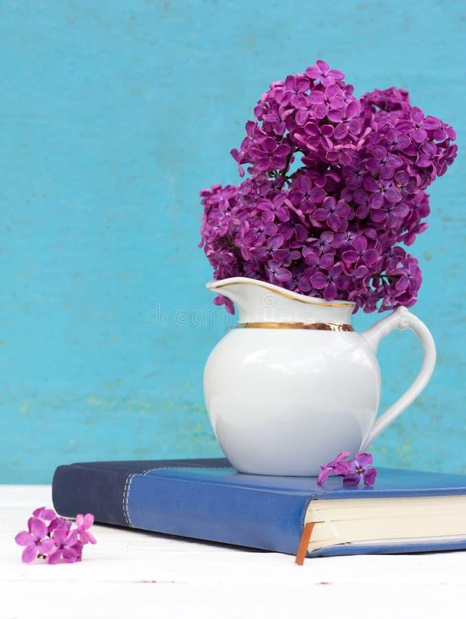 Um ramalhete de flores roxas lilás em um vaso branco fotografia de stock