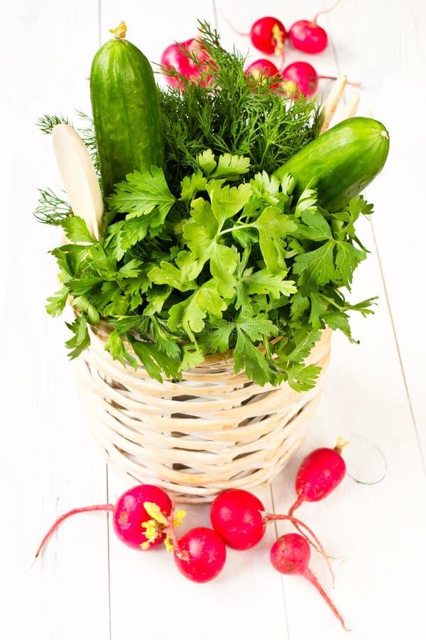 Um ramalhete de legumes frescos em uma cesta de vime da bacia em w branco imagem de stock royalty free