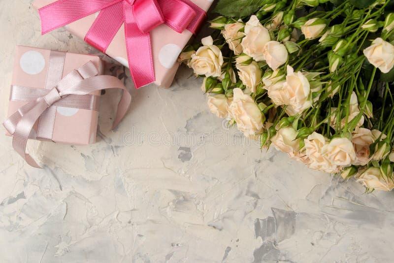 Um ramalhete de mini rosas macias bonitas e de uma caixa de presente em um fundo do betão leve Lugar para o texto feriados presen fotos de stock royalty free