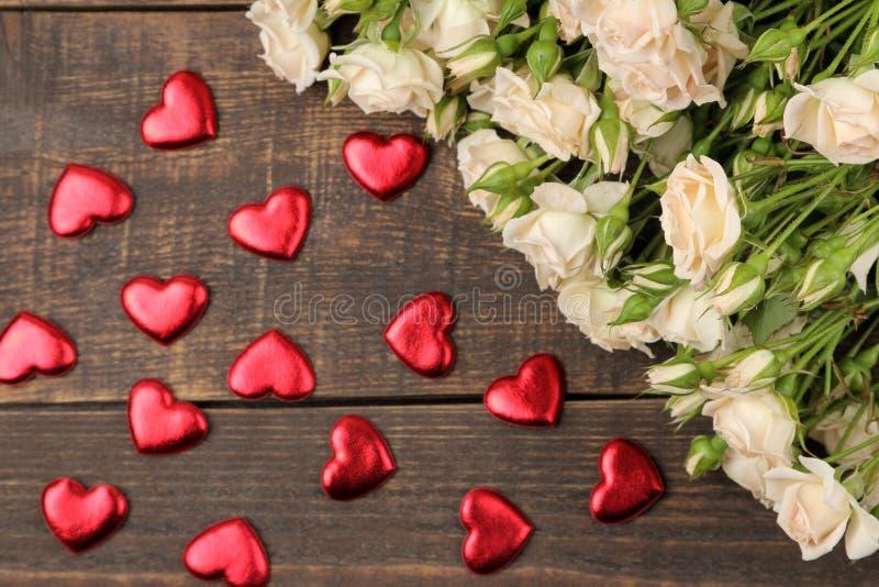 Um ramalhete de mini rosas macias bonitas em uma tabela de madeira marrom com corações Vista superior foto de stock