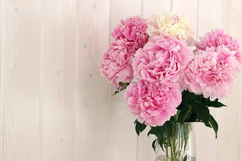 Um ramalhete de peônias cor-de-rosa cortadas do jardim em um vaso de vidro transparente contra uma parede de madeira branca Estil imagem de stock