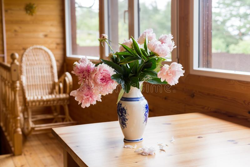 Um ramalhete de peônias da mola em um vaso em uma tabela em um terraço acolhedor fotografia de stock royalty free