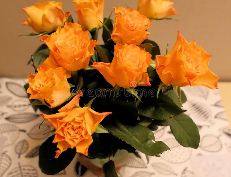 Um ramalhete de rosas alaranjadas na tabela na sala foto de stock royalty free