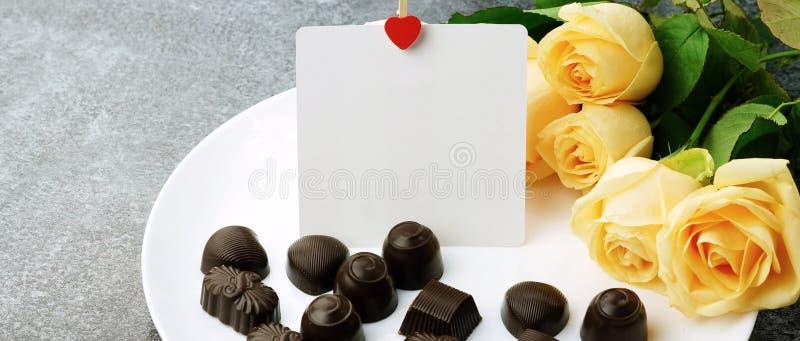Um ramalhete de rosas bonitas, de chocolates e de um cartão para o texto foto de stock