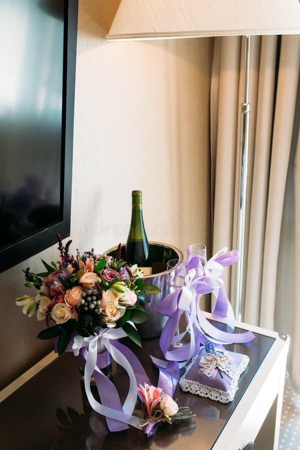 Um ramalhete do casamento, um boutonniere, uma garrafa do champanhe está na tabela fotos de stock royalty free
