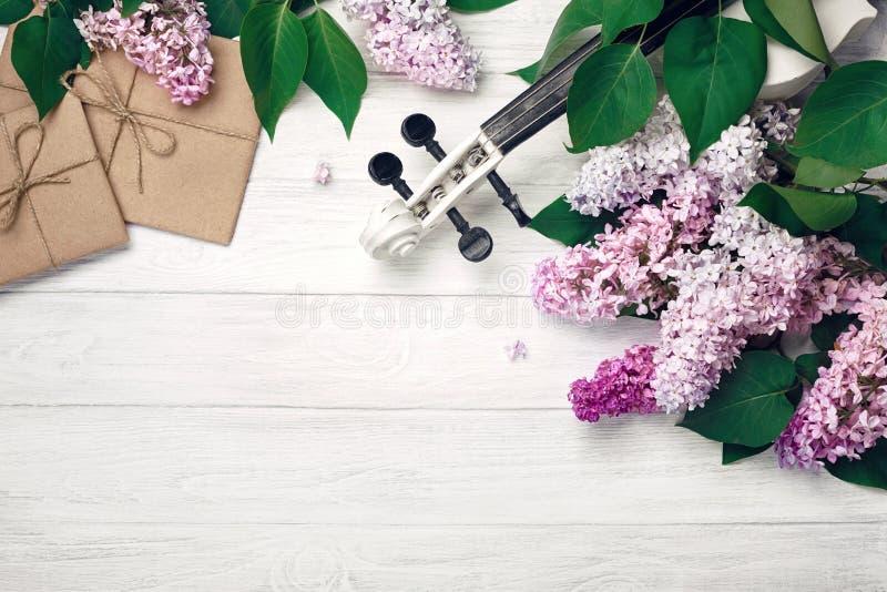 Um ramalhete dos lilás com a folha do violino, da letra e de música em uma tabela de madeira branca Wiev superior com espaço para foto de stock