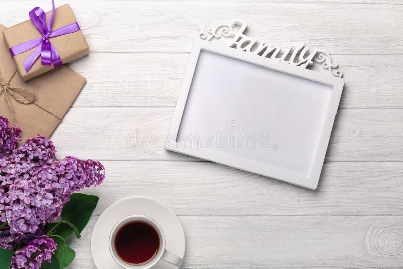 Um ramalhete dos lilás com um quadro branco para a inscrição, copo do chá, caixa de presente, envelope do ofício nas placas branc imagens de stock
