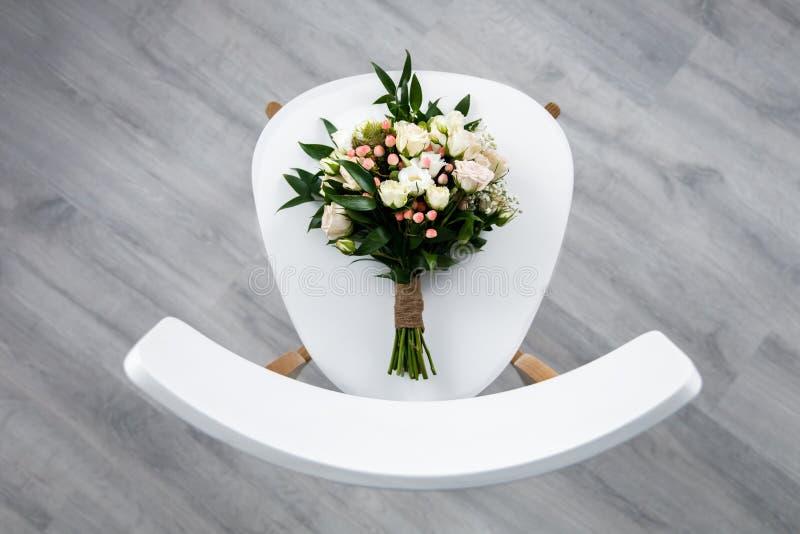 Um ramalhete elegante bonito para a noiva est? encontrando-se na cadeira imagens de stock royalty free