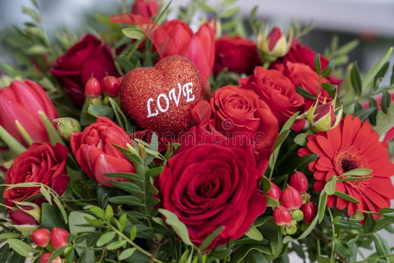 Um ramalhete festivo de uma variedade de flores vermelhas e um coração com o amor da inscrição para os outros feriados de Valenti fotos de stock royalty free