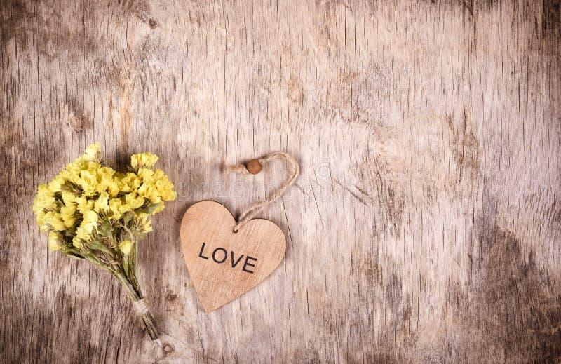 Um ramalhete pequeno de wildflowers amarelos das flores e de um coração de madeira Um símbolo do amor imagens de stock royalty free