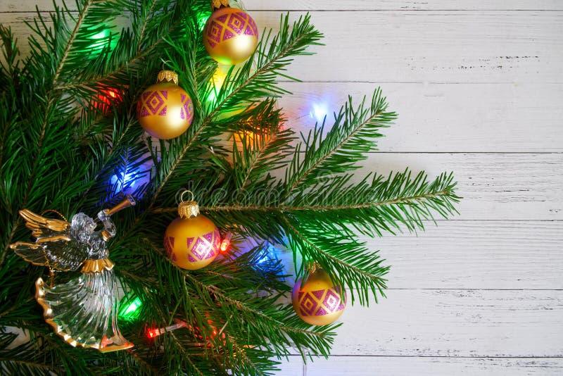 Um ramo de árvore do Natal decorado com brinquedos e luzes ao lado da fotos de stock
