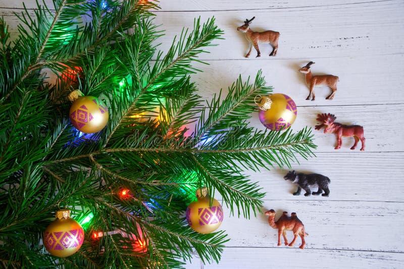 Um ramo de árvore do Natal decorado com brinquedos e luzes ao lado da imagem de stock