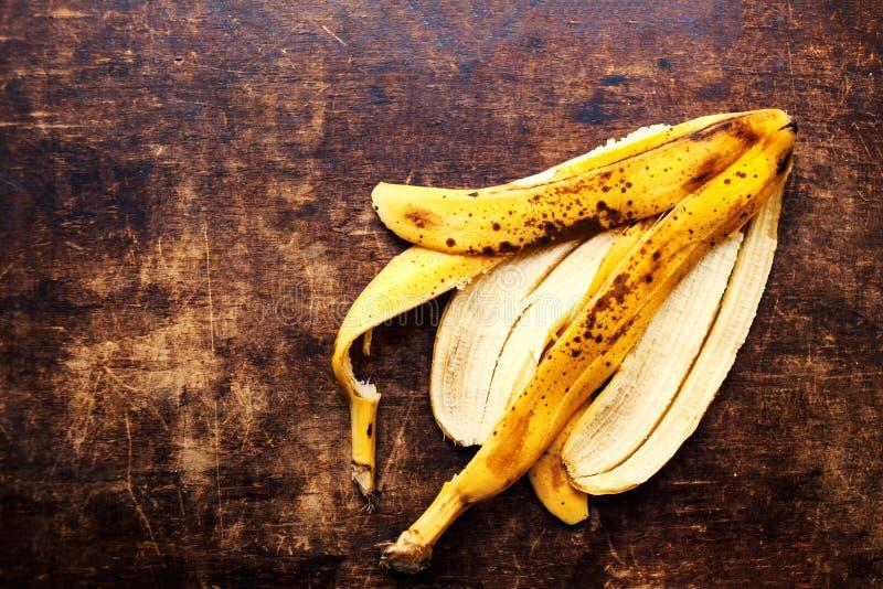 Um ramo de bananas maduras podres descasca no backgrou de madeira do vintage fotografia de stock