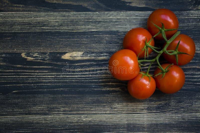 Um ramo de tomates vermelhos frescos em um fundo preto foto de stock royalty free