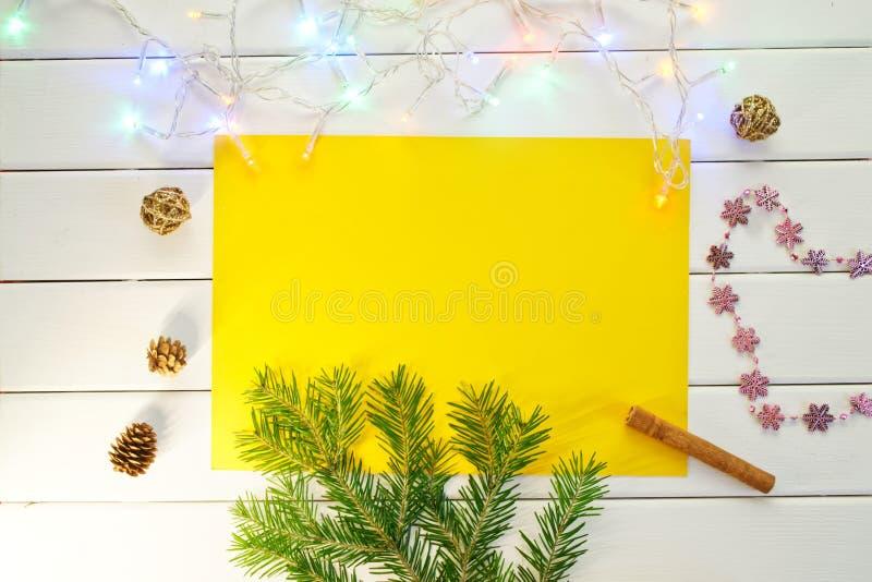 Um ramo de uma árvore de Natal, de uma festão e de cones em uma luz fotografia de stock