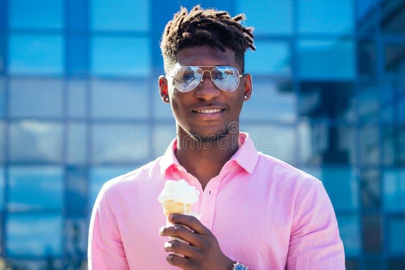 Um rapaz afro-americano, legal e elegante, apavora o cabelo em óculos escuros, tomando sorvete em uma buzina de waffle no verão. fotos de stock royalty free