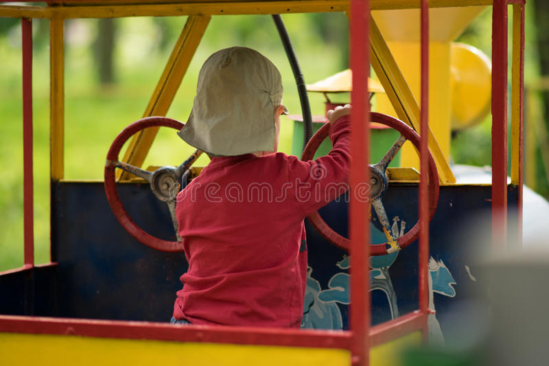 Um rapaz pequeno é de jogo e de condução um trem do brinquedo imagens de stock royalty free