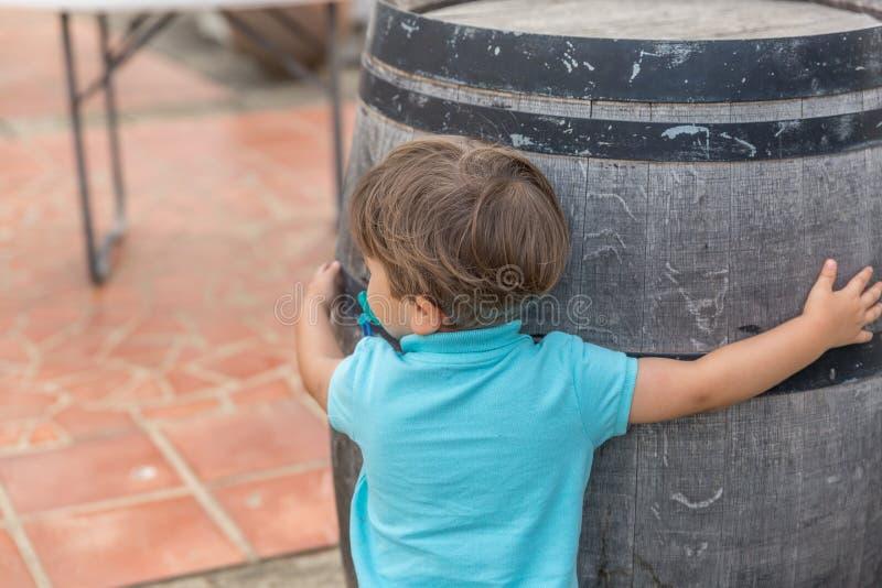 Um rapaz pequeno agradável vestido no azul com abraços de uma chupeta um o tambor fotografia de stock