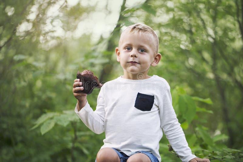 Um rapaz pequeno aprecia um queque do chocolate foto de stock