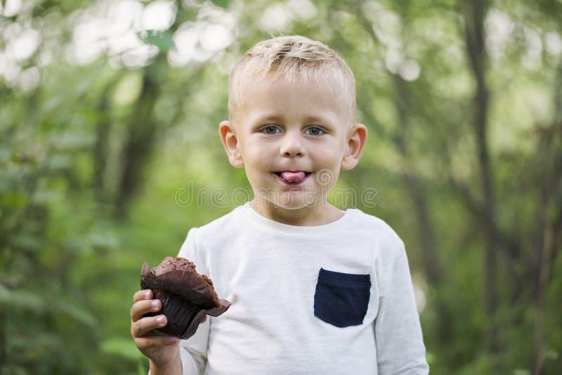 Um rapaz pequeno aprecia um queque do chocolate imagem de stock royalty free