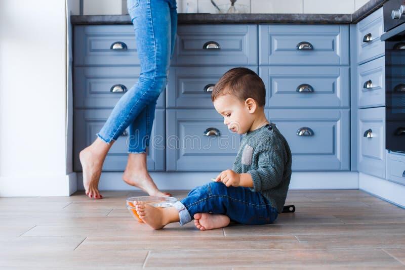 Um rapaz pequeno bonito está sentando-se no assoalho da cozinha com sua mãe no fundo foto de stock royalty free