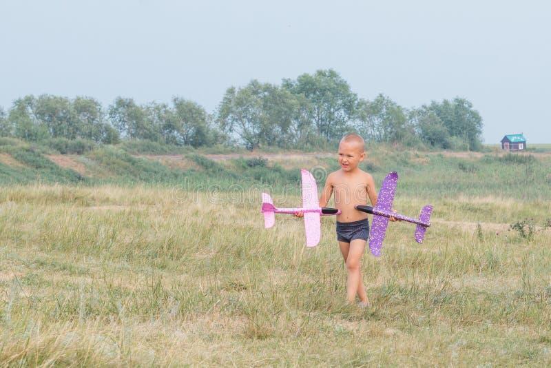 Um rapaz pequeno bonito no short anda através do campo e guarda dois planos do brinquedo em suas mãos imagem de stock