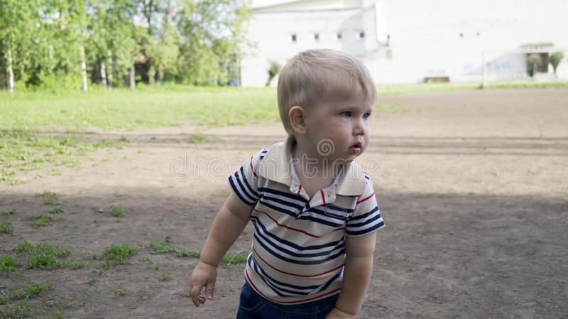 Um rapaz pequeno com caminhadas do cabelo branco no parque imagens de stock