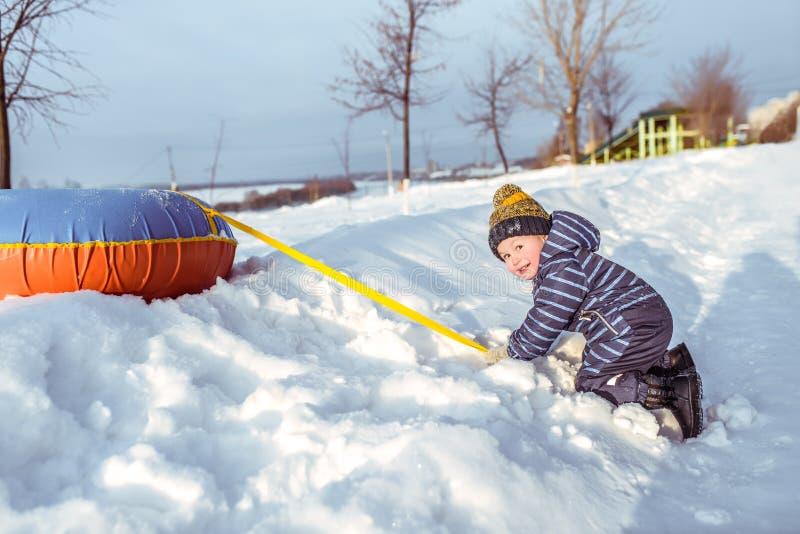 Um rapaz pequeno de 3 anos de jogos velhos em um monte no inverno, nas trações da neve e nas árvores Feriados nos feriados de inv fotografia de stock