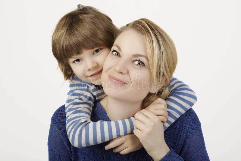 Um rapaz pequeno de sorriso e sua mãe que abraçam no fundo branco foto de stock