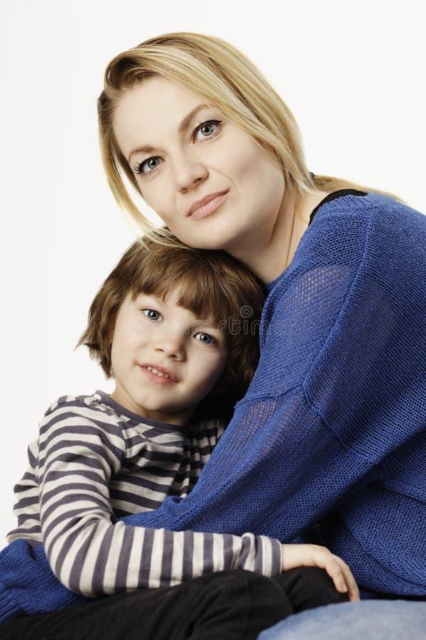 Um rapaz pequeno de sorriso e sua mãe que abraçam no fundo branco imagens de stock