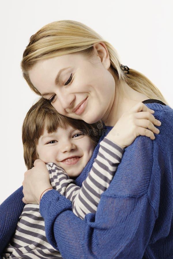 Um rapaz pequeno de sorriso e sua mãe que abraçam no fundo branco fotografia de stock royalty free