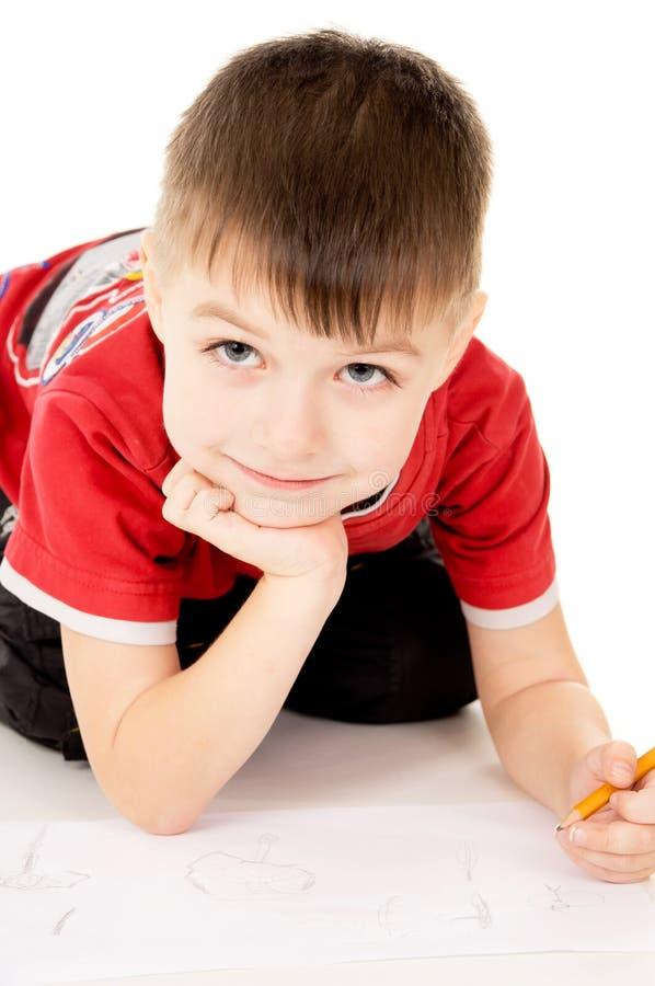 Um rapaz pequeno desenha no papel fotografia de stock royalty free
