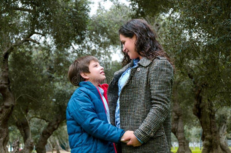 Um rapaz pequeno e sua mãe olham se e riem imagem de stock