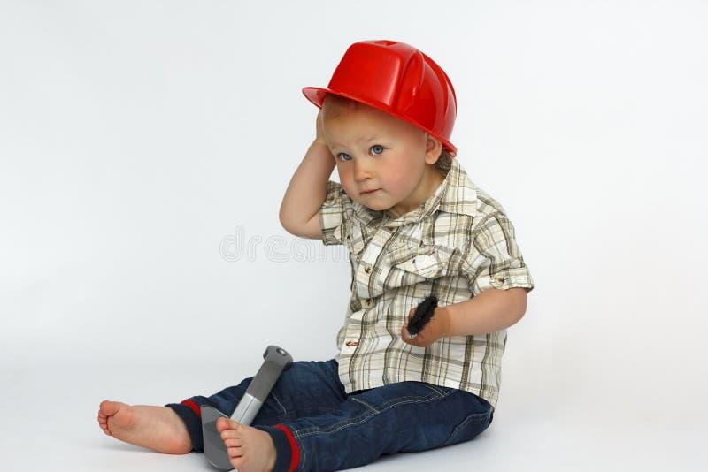 Um rapaz pequeno em um capacete de segurança da construção imagem de stock