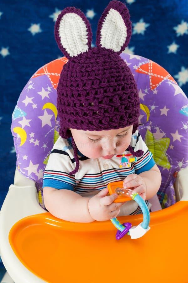Um rapaz pequeno em um chapéu feito malha com orelhas de coelho joga foto de stock royalty free