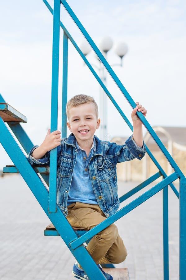 Um rapaz pequeno em uma caminhada escalada em uma estrutura do metal foto de stock