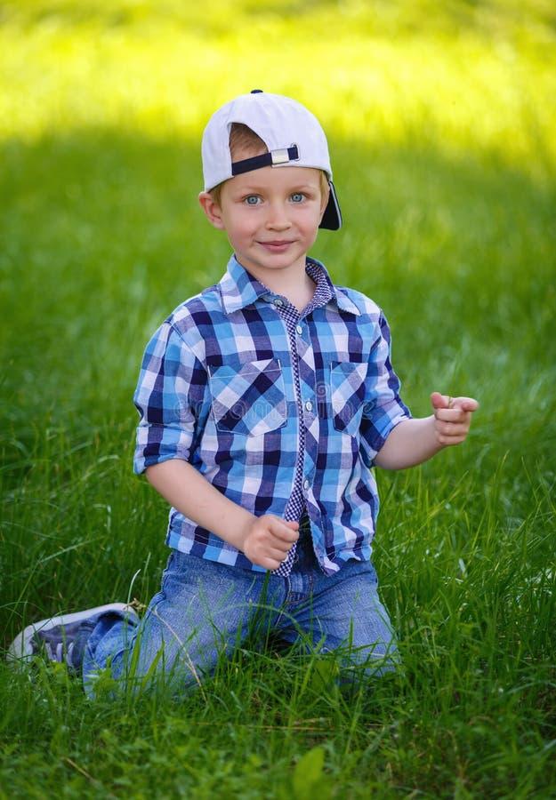 Um rapaz pequeno em uma camisa de manta azul está sentando-se na grama verde fotografia de stock royalty free