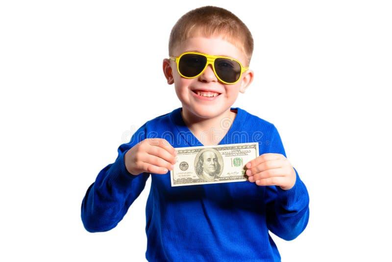 Um rapaz pequeno em uma camiseta azul sorri e guarda cem dólares foto de stock