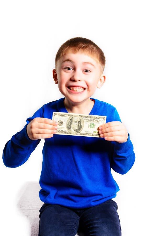 Um rapaz pequeno em uma camiseta azul sorri e guarda cem dólares foto de stock royalty free