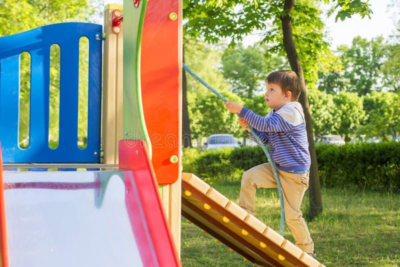 Um rapaz pequeno escala o monte do ` s das crianças que guarda a corda Brincadeiras em um campo de jogos do ` s da criança imagem de stock royalty free