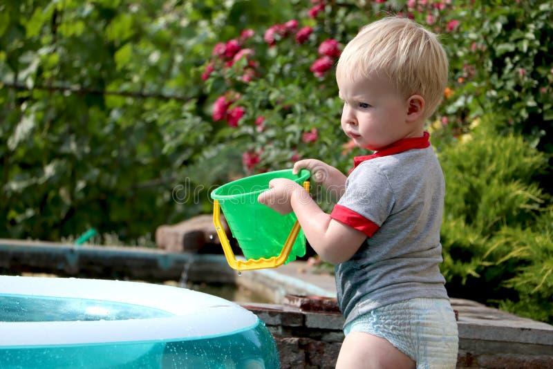 Um rapaz pequeno está jogando com água perto de uma associação inflável Feriados do verão e da família Infância feliz foto de stock royalty free