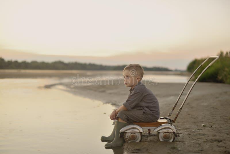 Um rapaz pequeno está jogando no banco de rio arenoso no verão no por do sol imagem de stock royalty free