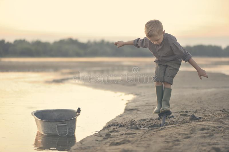 Um rapaz pequeno está jogando no banco de rio arenoso no verão no por do sol fotos de stock