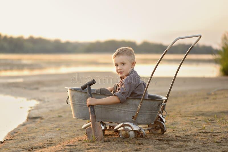 Um rapaz pequeno está jogando no banco de rio arenoso no verão no por do sol foto de stock royalty free