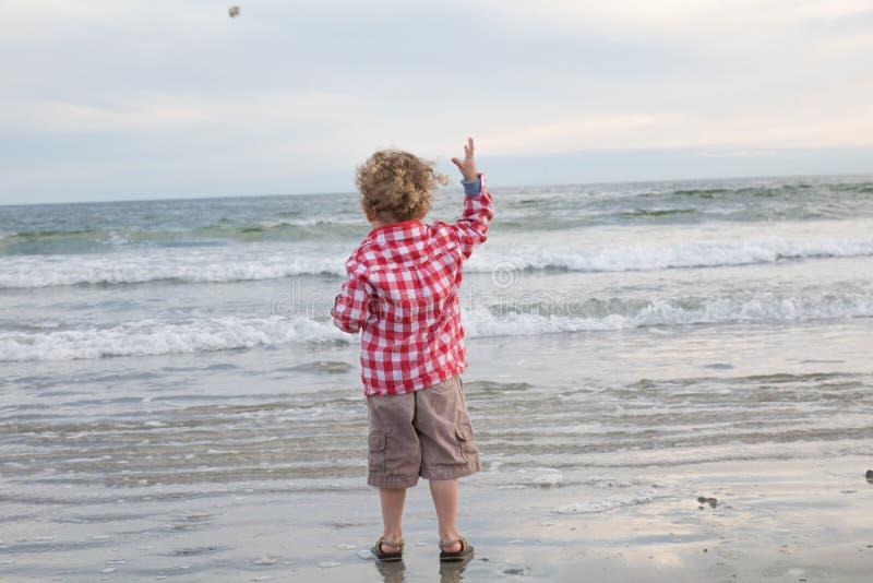 Um rapaz pequeno está jogando uma rocha no oceano fotografia de stock royalty free