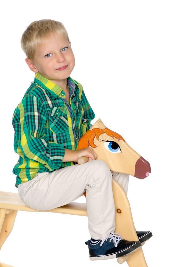 Um rapaz pequeno está montando um cavalo de madeira imagem de stock