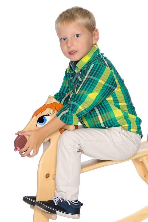 Um rapaz pequeno está montando um cavalo de madeira imagens de stock
