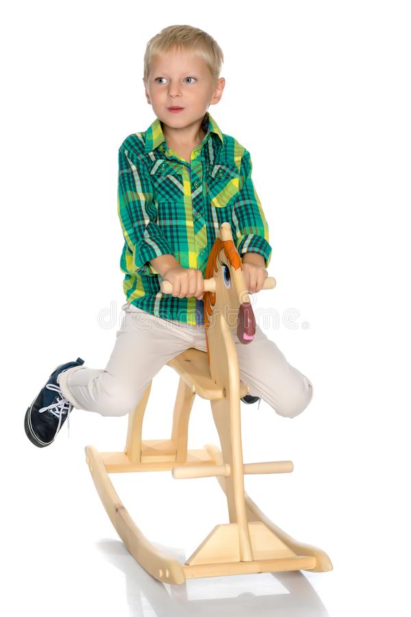 Um rapaz pequeno está montando um cavalo de madeira foto de stock