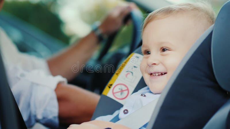 Um rapaz pequeno está sentando-se em um banco de carro perto de seu pai, sorrindo felizmente Conceito - segurança e cuidado imagens de stock royalty free